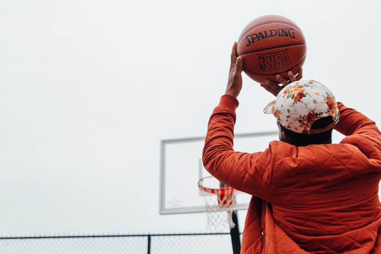 person aiming to shoot ball in basketball ring