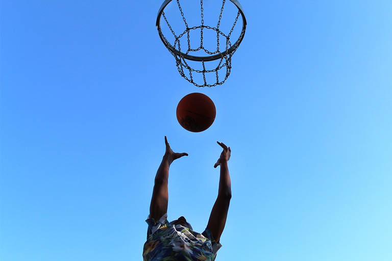 person about to dunk ball in basketball ring