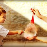 Little boy popping the water balloon